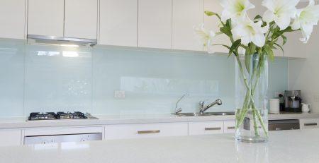Flowers on white kitchen bench with splashback
