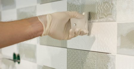 white and grey tiles with person grouting